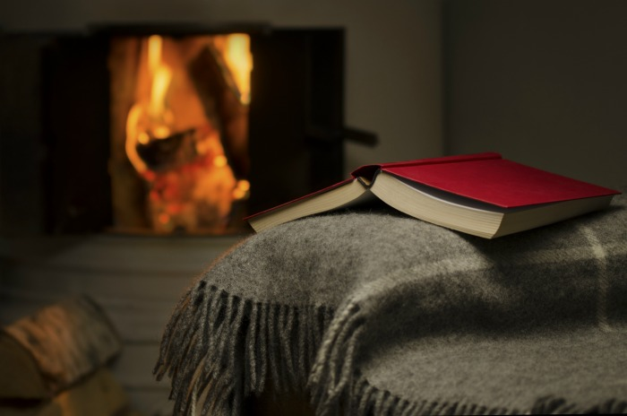 Fireplace with a book on a throw