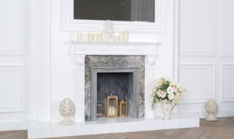 white empty fireplace with lanterns, candles and flowers