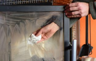 Man's hands cleaning fireplace glass