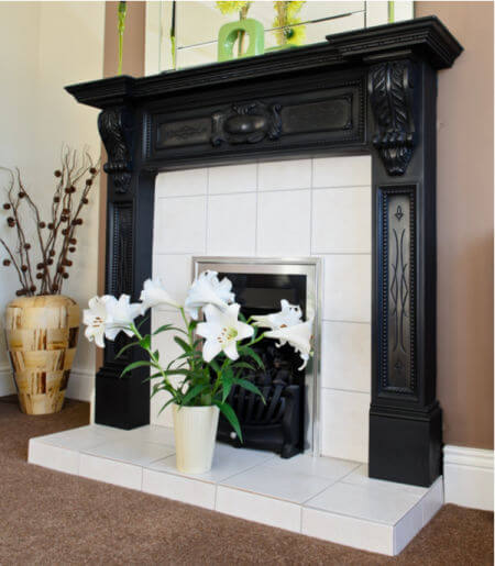 Fireplace decorated for summer with lily flower on hearth