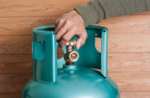 LPG tank with valve being opened by hand